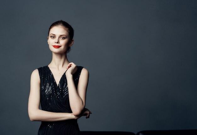 Mulher linda em um vestido preto, moda, estilo de vida, fundo escuro