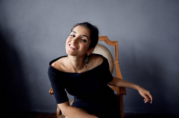 Mulher linda em um vestido preto perto da cadeira de fundo isolado de moda de luxo