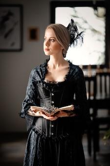 Mulher linda em um vestido preto segurando um livro e flores de lavanda dentro de casa