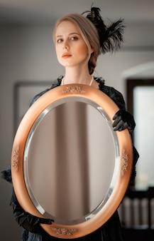 Mulher linda em um vestido preto vintage segurando um espelho no interior