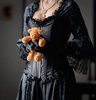 Mulher linda em um vestido preto vintage segurando um ursinho de pelúcia