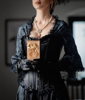 Mulher linda em um vestido preto vintage segurando uma caixa de presente no interior