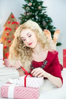 Mulher linda em um vestido vermelho com muitas caixas de presente. conceito de natal. decoração de natal