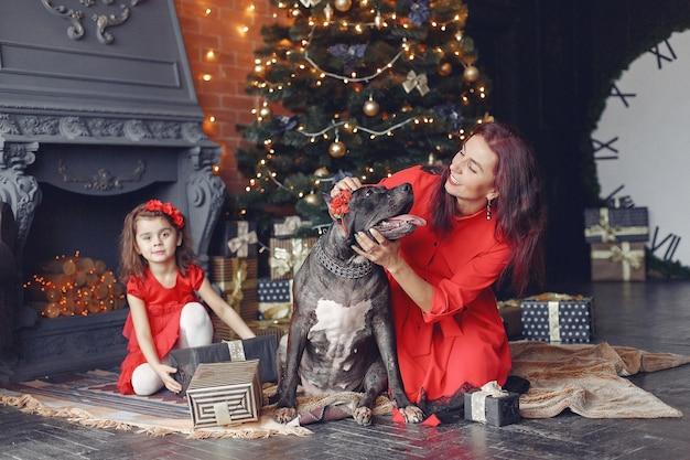 Mulher linda em um vestido vermelho. família em casa. mãe com filha. pessoas com um cachorro.