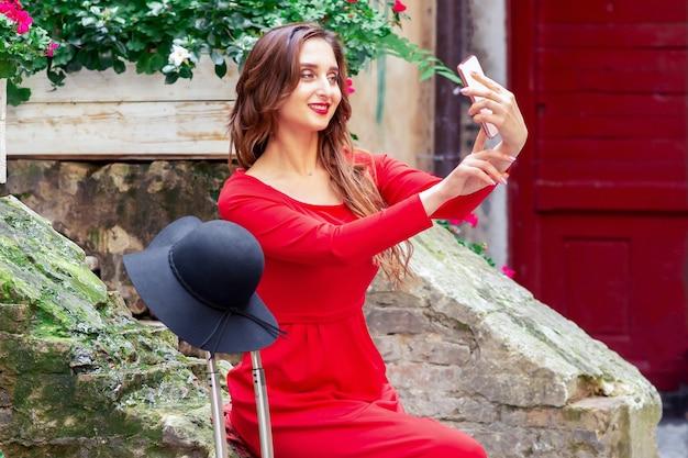 Mulher linda em um vestido vermelho leva selfie na rua da cidade.