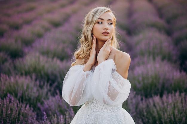 Mulher linda em vestido de noiva em campo de lavanda
