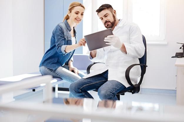 Mulher linda encantada alegre sorrindo e apontando para a tela do tablet enquanto está sentada perto de seu médico