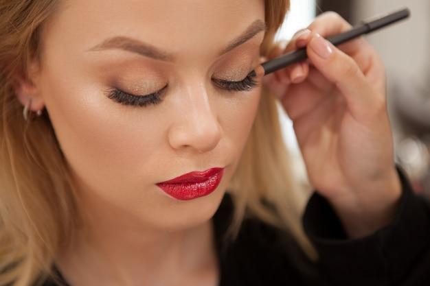 Mulher linda fazendo maquiagem profissional