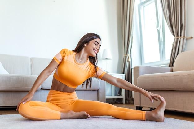 Mulher linda fitness fazendo exercícios de aquecimento em casa
