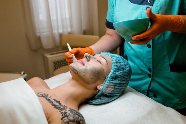 Mulher linda garota natural no salão spa, faz uma máscara facial, procedimento de rejuvenescimento facial