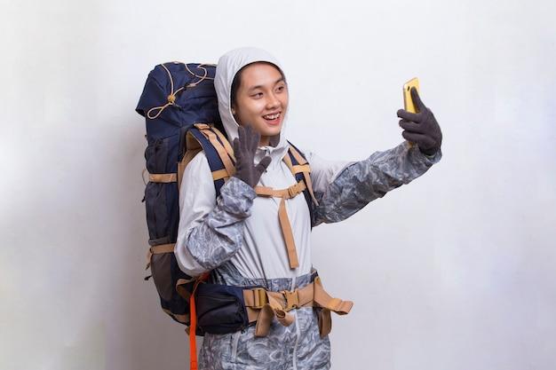 Mulher linda jovem alpinista asiática usando telefone celular isolado no fundo branco