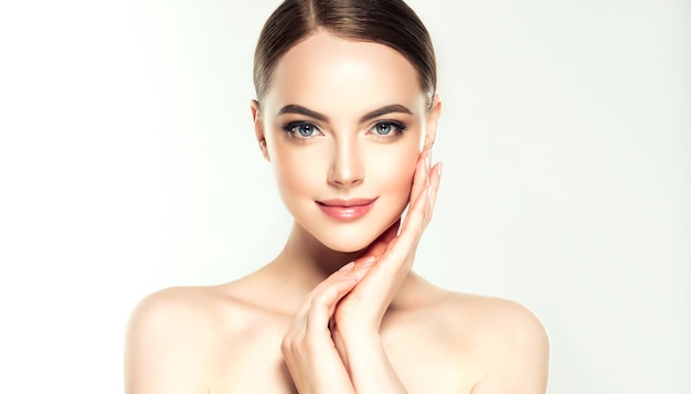 Mulher linda, jovem, de cabelos castanhos, pele limpa, fresca e maquiagem delicada tocando o rosto.