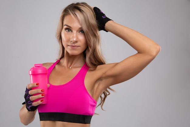 Mulher linda jovem fitness em uma camiseta esportiva brilhante com água para beber durante um treino.