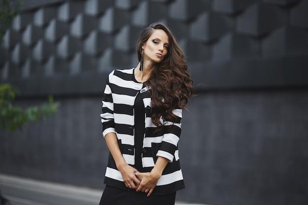 Mulher linda jovem modelo com cabelo escuro perfeito, usando um vestido de noite preto e jaqueta olhando para ...