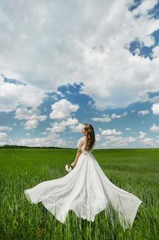 Mulher linda jovem modelo com penteado de casamento em vestido longo branco, posando em um campo verde no dia ensolarado de verão