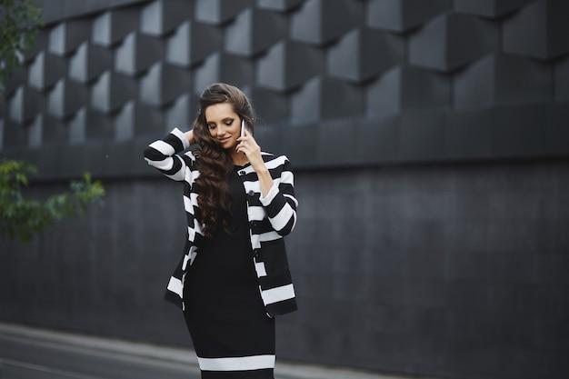 Mulher linda jovem modelo em roupa elegante, falando ao telefone ao ar livre jovem bonita fashione ...