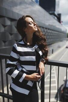 Mulher linda jovem modelo vestindo jaqueta e vestido preto, aproveitando o dia ensolarado de verão na cidade youn ...