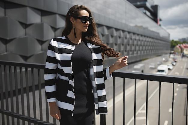 Mulher linda jovem modelo vestindo jaqueta preta vestido e óculos de sol, aproveitando o dia ensolarado de verão na ...