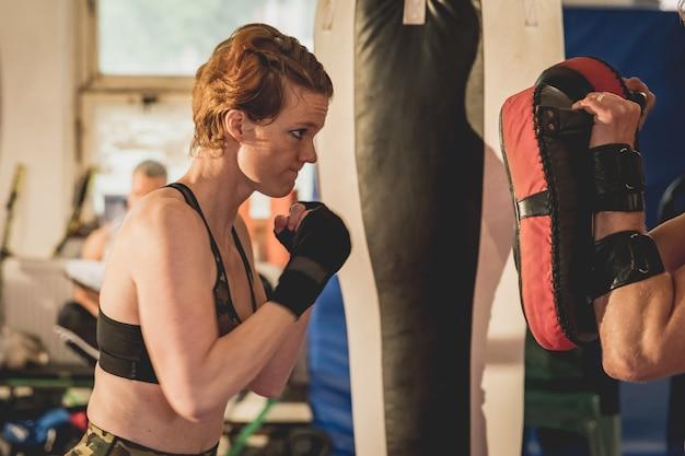 Mulher linda, lutador de mma no ginásio durante o treino. preparando-se para uma partida difícil