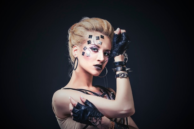 Mulher linda modelo com arte corporal em face de roupas incomuns e da moda