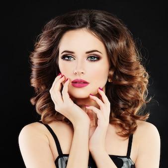 Mulher linda modelo com cabelo castanho cacheado e maquiagem perfeita. unhas de penteado, maquiagem e manicure da moda. glamorous beautyke-up e manicure nails