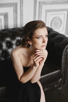 Mulher linda modelo com olhos azuis profundos, maquiagem e penteado à noite, usando um vestido preto posando no sofá vintage dentro de casa