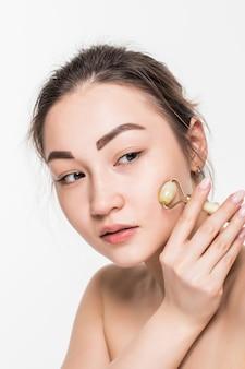 Mulher linda modelo com pele limpa fresca saudável, desfrutando de uma massagem com um rolo de rosto de jade para melhorar a circulação, relaxar os músculos e tonificar a pele, isolada na parede cinza com espaço de cópia