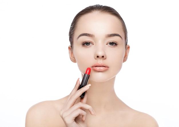 Mulher linda modelo segurando maquiagem tubo de batom