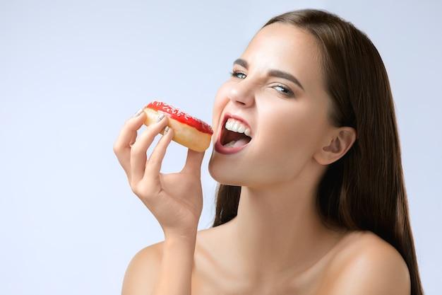 Mulher linda mordendo um donut