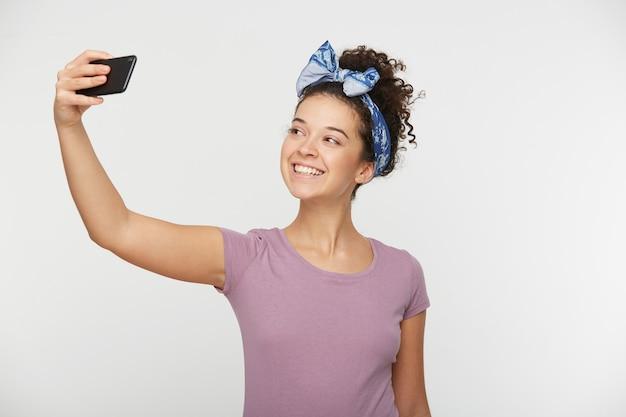 Mulher linda morena atraente alegre com cabelo encaracolado em uma camiseta casual e bandana fazendo uma foto de selfie