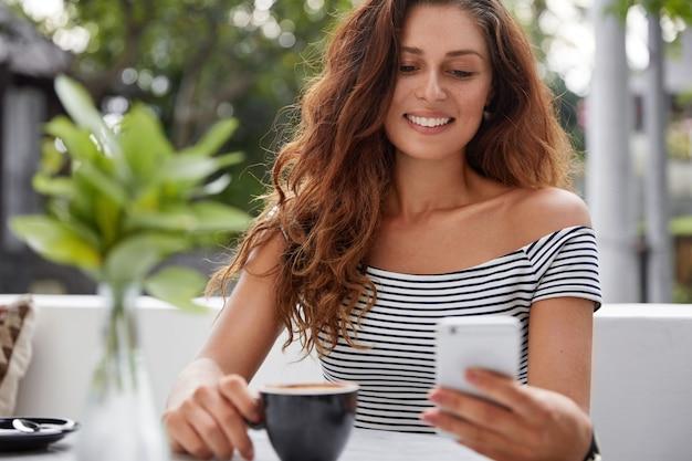 Mulher linda morena com mensagens de texto de expressão alegre no smartphone e bebe café aromático