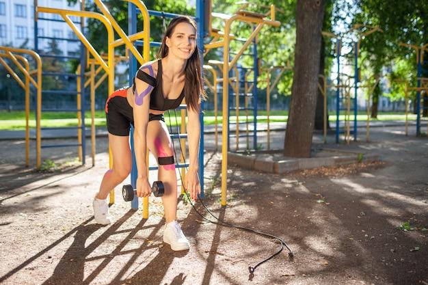Mulher linda morena em forma treinando com halteres no parque