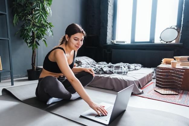 Mulher linda morena fitness fazendo exercícios de alongamento na frente do laptop, fazendo ioga dentro de casa, em casa