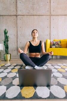 Mulher linda morena fitness fazendo ioga na frente do laptop, meditar dentro de casa em casa. estilo de vida saudável