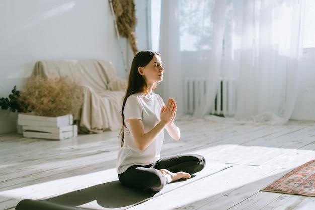 Mulher linda morena fitness meditando, fazendo ioga dentro de casa em casa