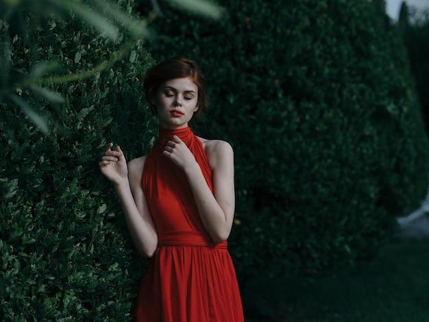 Mulher linda mulher vestida de vermelho ao ar livre perto de encanto de luxo de bush.