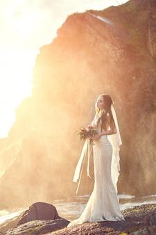 Mulher linda noiva em pé nas rochas por mar