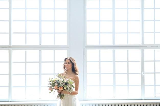 Mulher linda noiva em um vestido de noiva elegante com buquê de flores