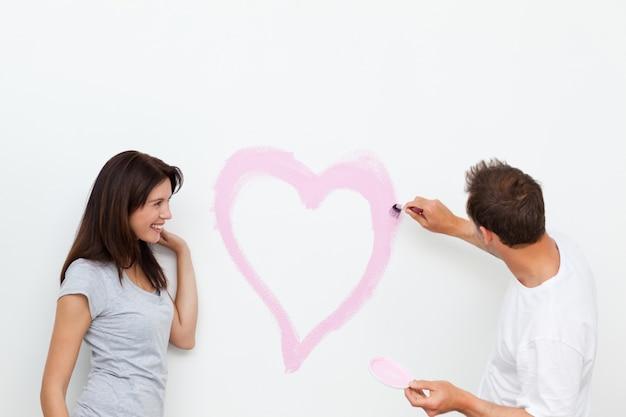 Mulher linda olhando seu namorado pintando um coração