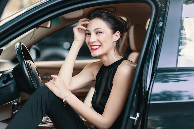 Mulher linda rindo, feliz enquanto está sentado no banco da frente