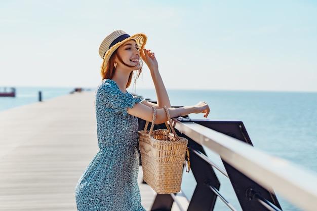 Mulher linda ruiva posando em um dia ensolarado caminha ao longo do cais perto da garota do mar usando fashionab.