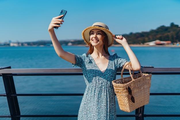 Mulher linda ruiva posando em um dia ensolarado, fazendo selfie usando caminhadas telefônicas ao longo do cais perto do s ...