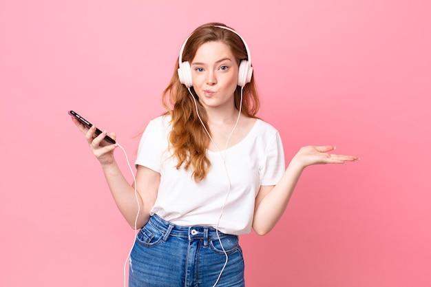 Mulher linda ruiva se sentindo intrigada e confusa e duvidando com fones de ouvido e smartphone