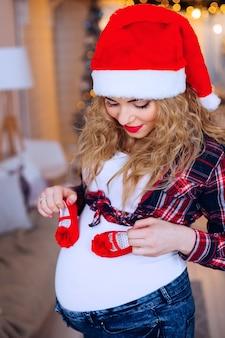 Mulher linda sapatinhos de bebê vermelho com chapéu de papai noel segurando perto de sua barriga