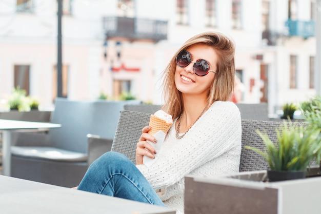 Mulher linda sentada em um café tomando sorvete em uma casquinha de waffle