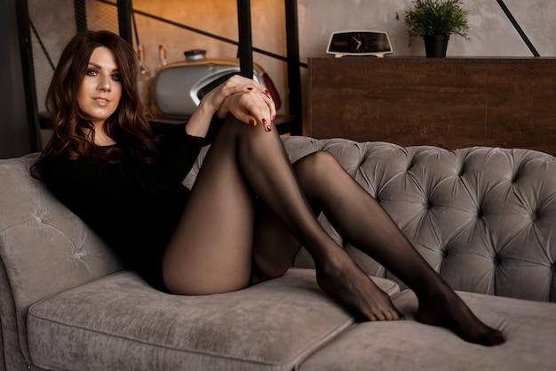 Mulher linda sexy com cabelo comprido e meia-calça preta transparente deitada em um sofá