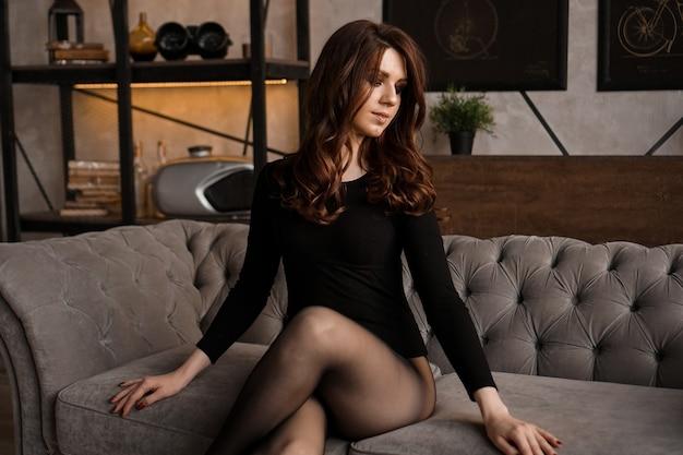 Mulher linda sexy com cabelo comprido e meia-calça preta transparente em um sofá