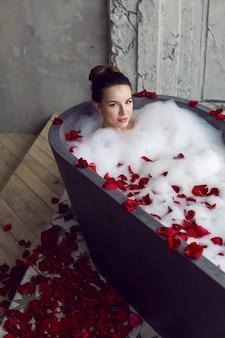 Mulher linda sexy deitada em uma banheira de pedra com espuma e pétalas