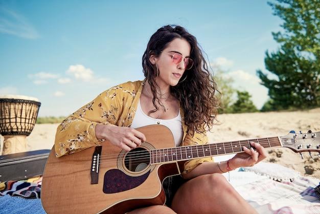 Mulher linda tocando violão na praia
