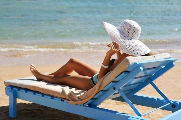 Mulher linda tomando banho de sol na praia de resort tropical